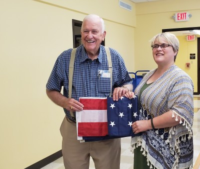 Richard Turner presents WBHML Director Monica Edwards with a new flag.