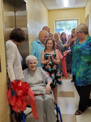 Blanche Trimble cuts the ribbon to the new elevators with help from Kathy Grace.