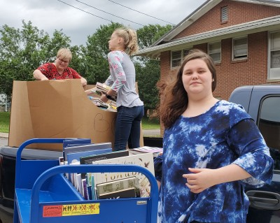 Our student assistants Danni and Eternity help Director Monica Edwards unload donated books.